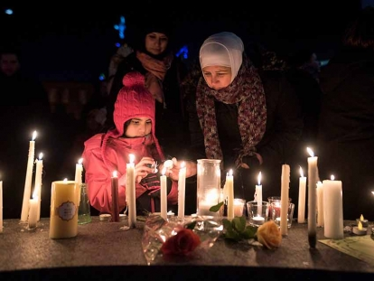 Sawsan Idris, right, lights candles with her daughters Lara (left) and Tamara while attending a vigil in Moncton, N.B. on Jan. 30, 2017 for the victims of the shooting.
