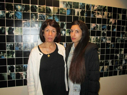 Rehab Nazzal with her daughter Rana Nazzal in front of photos of a raid on Palestinian prisoners. Smiling didn't seem appropriate given the context.