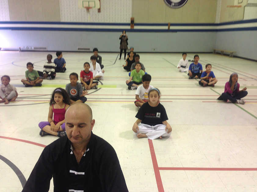 Martial Arts instructor Mohammed Al Nuiaimi leads students in quiet meditation.