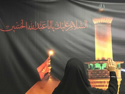 "A banner like this is found in many Twelver Shia mosques. The words in red read « Al Salaam Aleika ya Aba Abdilla Al Hussain (Peace be on you, Hussain father of Abdallah) ». The hand gesture is symbolic., it's a form of salutation to  Imam Hussain (pbuh) and to those who have suffered on Ashura. This hand gesture is make when Shia Muslims read a type of prayer called  a « Ziyarat ». The prayer is taken from the Quran : ""And never think of those who have been killed in the cause of Allah as dead. Rather, they are alive with their Lord, receiving provision"" 3:169."