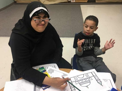 Aaliya Jaffer volunteers to help Mikail Abbas with his craft project during Muharram 2018 at the Jaffari Community Centre.
