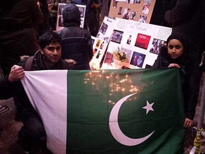 At the vigil held in front of City Hall, university students Samer Abed and Sonia Hamid hold a Pakistani Flag in front of the pictures of those killed in the Peshawar School Attack.