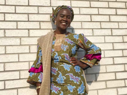 Yoruba Nigerian Canadian Suliya Mazou sporting an ankara print dress and gele (headwrap).