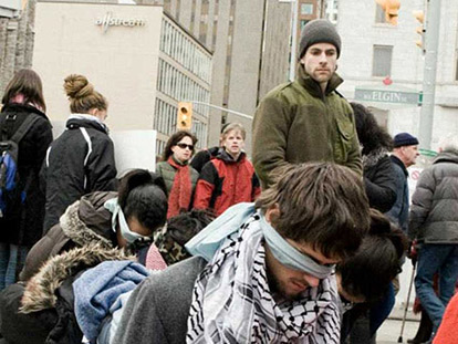Actors kneel in line at a mock Israeli checkpoint recreated in Ottawa.